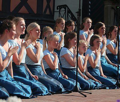 Sänger sitzen zum Brahms Chorfestival auf der Bühne vor dem Rathaus