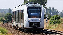 abelio Zug fährt auf Schienen durch die Natur