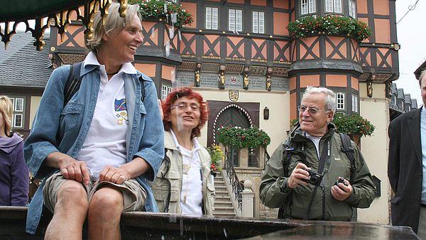 Eine Pilgerin kühlt sich die Beine im Marktbrunnen auf dem Marktplatz in Wernigerode