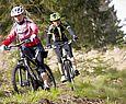 Zwei Frauen auf dem Mountainbike fahren durch den Wald