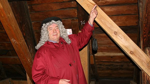 Meister Hilleborch steht auf dem Dachboden des Rathauses