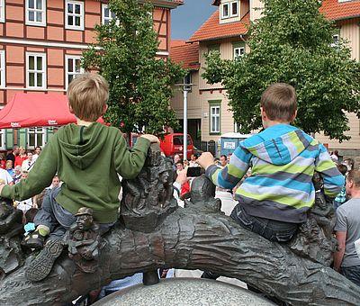 Zwei Kinder sitzen auf dem Nicolaibrunnen zum Rathausfest in Wernigerode