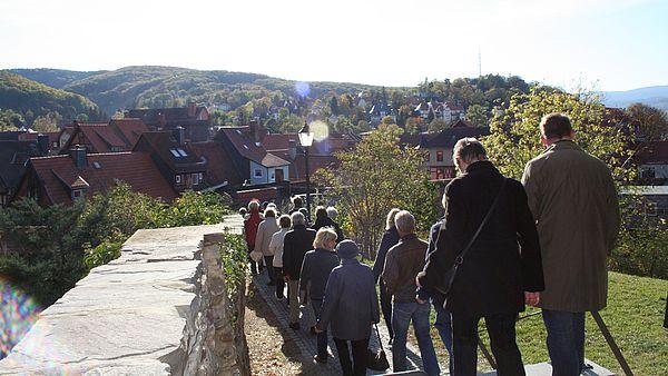 Gruppe von Personen läuft entlang der Stadtmauer