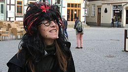 Stadtführerin im Kostüm einer Hexe auf dem Marktplatz