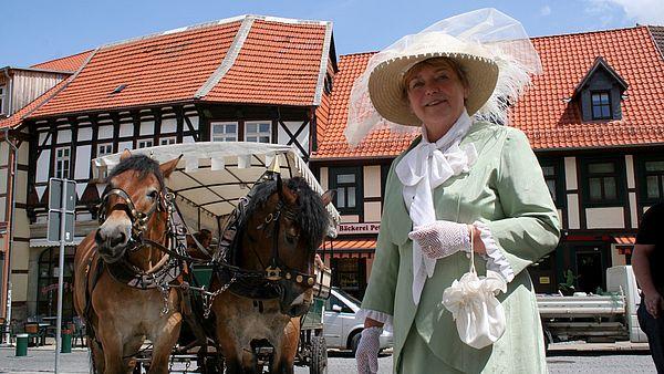 Eine Gästeführerin im Kostüm steht vor einer Pferdekutsche
